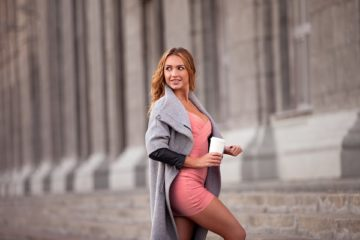 Stylish Russian woman wearing a beautiful pink dress with a coat