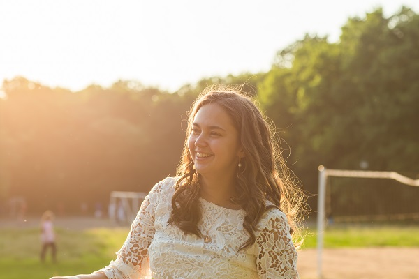 The portrait of young smiling Russian bride in the summer park