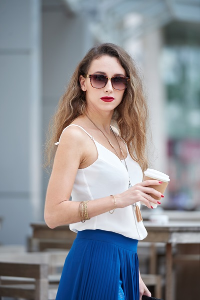 Perfect-looking stylish Russian lady with a cup of coffee and sun-glasses