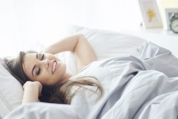Smiling Russian woman lying on the bedroom all alone