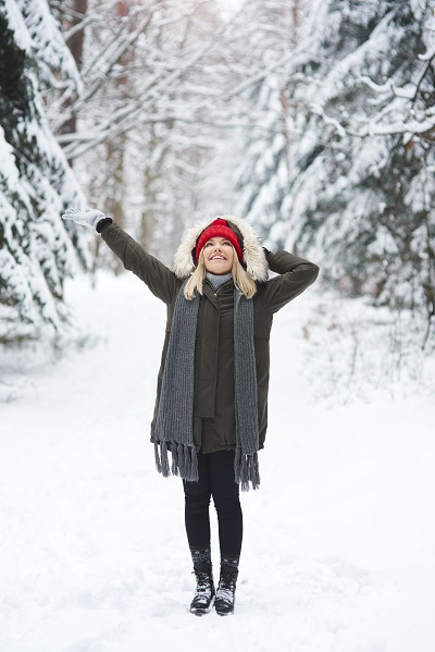 Joyful Russian girl standing in the forest in wintertime with one hand up