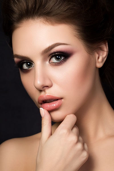Portrait of a beautiful young Russian woman with an evening makeup touching her lip with a finger